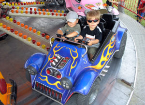 young boys riding amusement ride in proper safety position